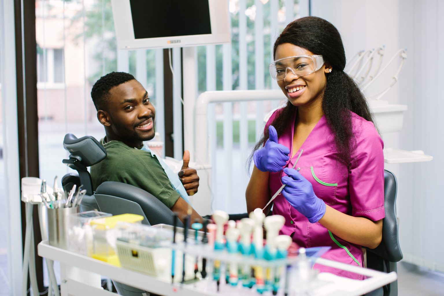 Dental Concept. Pretty African Female Dentist In Pink Suit, Protective Glasses And Blue Latex Gloves Shows Ok Sign And Smiling. Young Male African Patient Sitting In The Dental Chair And Smiling