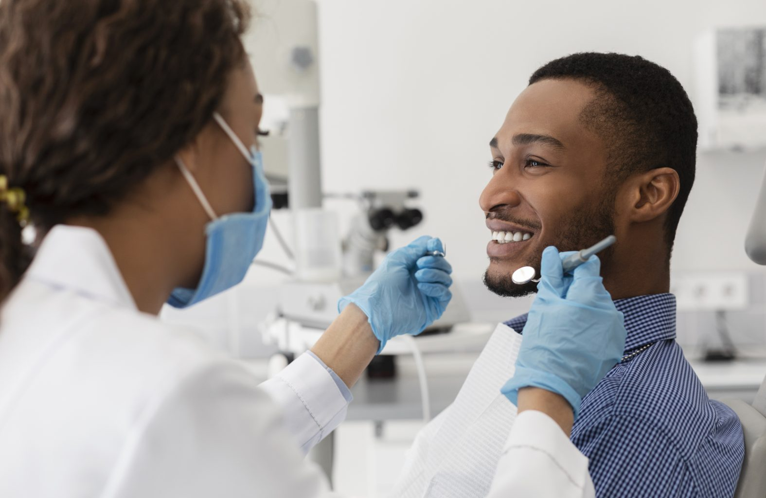 Young African Guy Smiling To His Female Dentist